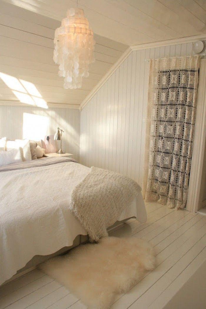 Scandinavische slaapkamer in warme wittinten en leuk kanten gordijn voor de deur.