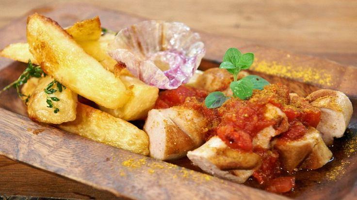 Currywurst mit Pommes Frites in einer Holzschale