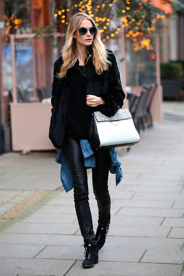 Street style look com calça de couro preta, blusa, casaco peludo maxi e botas.