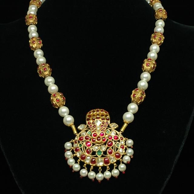 A 20th century South Indian Naga pendant originally designed as a hair ornament. This rich 22K gold gem-set piece has been hung on a strand of very fine pure white Japanese Akoya pearls and Burmese ruby set in 22K gold beads. The pendant, which represents a cobra canopy lingam, is set with very high quality Burmese rubies, magnificent Indian Golconda diamonds, and Colombian emeralds. The original Basara pearls were replaced with matching pure white Akoya pearls and red enamel tips.