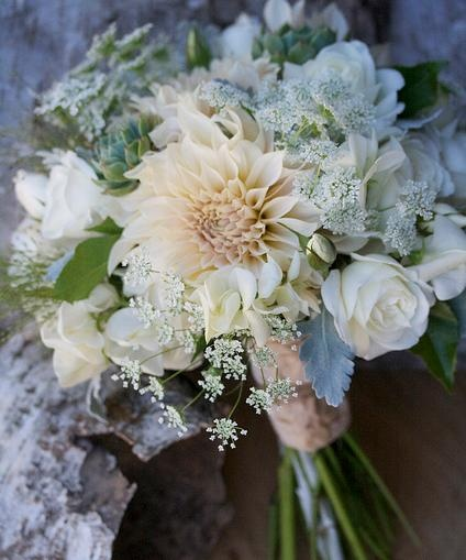 The bridal bouquet will be a textural round clutch of burgundy dahlias and dahlia buds, ivory spray roses, orange ranunculus, burgundy scabiosa and scabiosa buds, ivory queen anne's lace, scabiosa pods, yellow craspedia and seeded eucalyptus wrapped in ivory ribbon with the stems showing