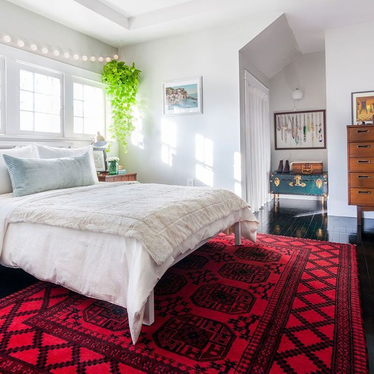 Bedroom With White Walls, Hanging Plant, Red Rug, And Wood Dresser.