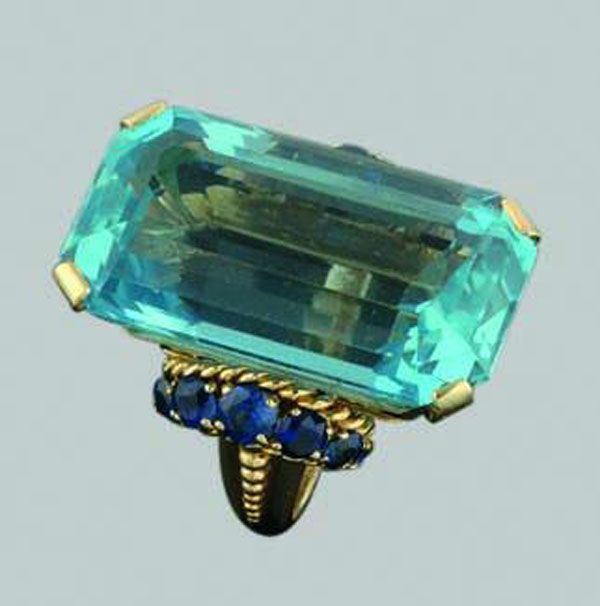 Boucheron aquamarine and sapphire cocktail ring set in 18ct yellow gold with a large emerald cut aquamarine weighing 36.0cts, a four claw raised pierced basket setting, six graduated blue sapphires set to each shoulder, granule decorations and a reeded band, engraved and signed  circa 1950