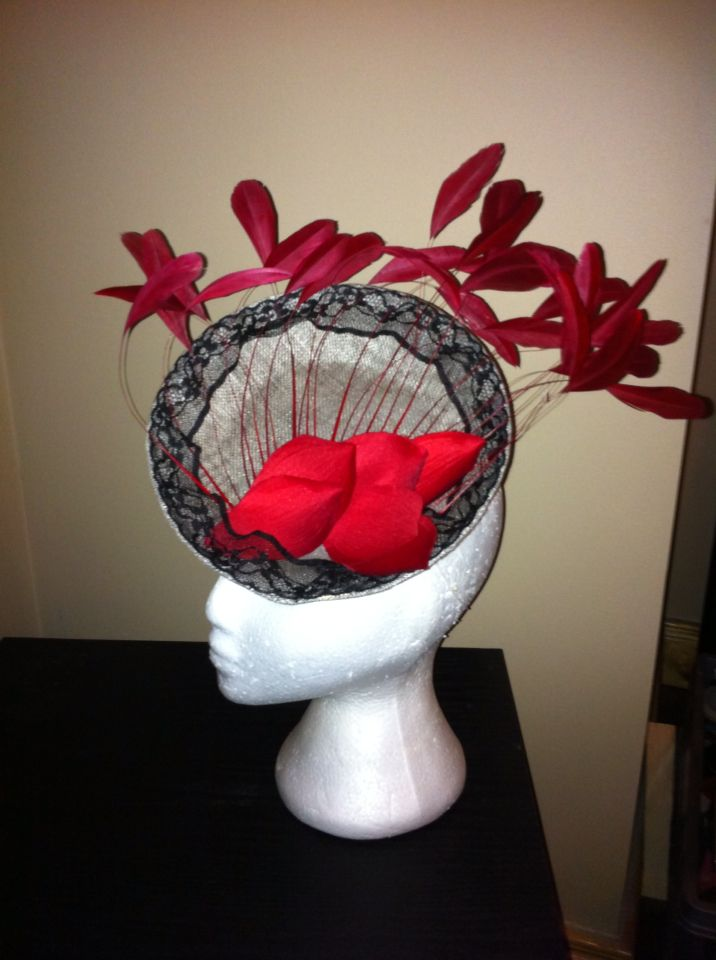 Silver base trimmed with black lace, red petals and spray of feathers.