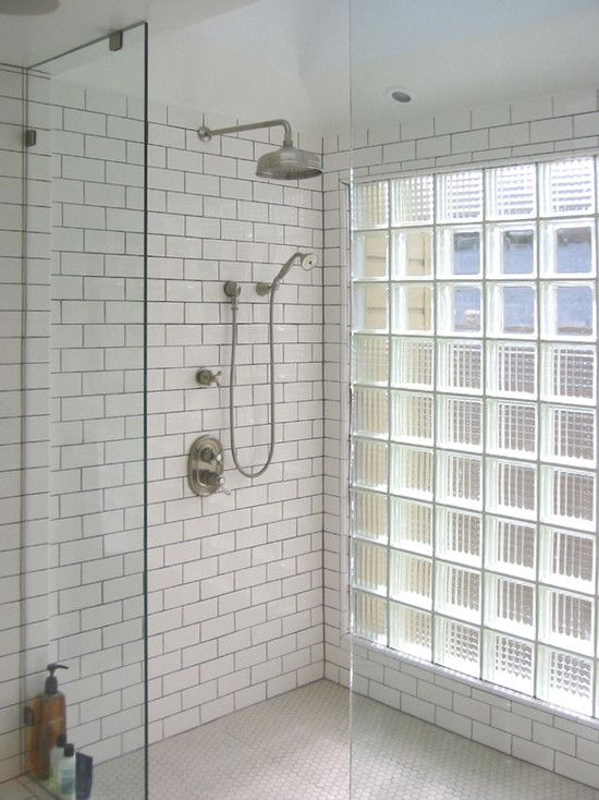 Subway tiles, industrial shower head, glass bricks.