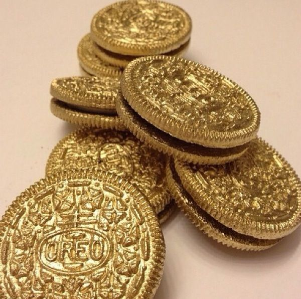 Edible gold oreo cookies painted with Duff cake graffiti in metallic gold.