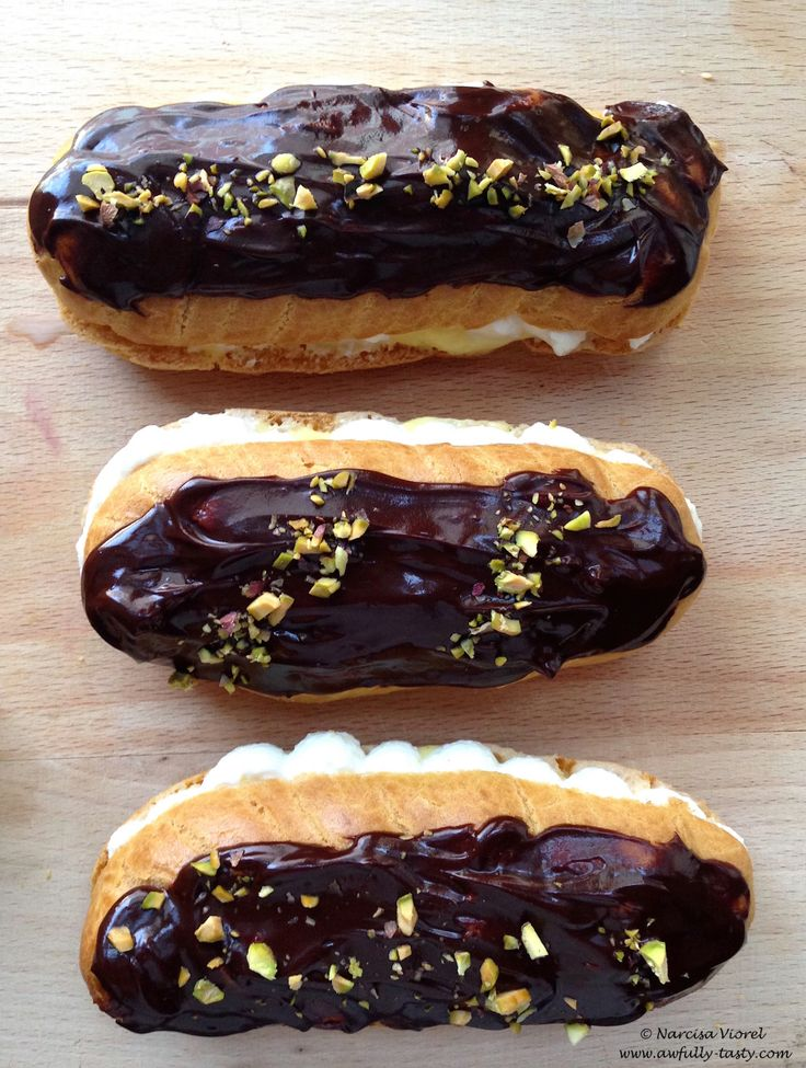 Eclere cu crema de vanilie si ciocolata.   Homemade eclairs filled with vanilla cream, whipped cream, chocolate glaze and chopped pistachio.