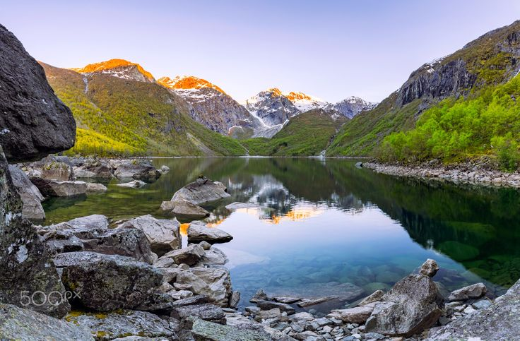 "The Lush Glacial Valley - The lush glacial valley ""Bondhusdalen"" in Norway. This postcard location have a breathtaking view with immense boulders strewn across the lake after the glacier ""Folgafonna"" receeded from the valley, leaving a lush fertile place."