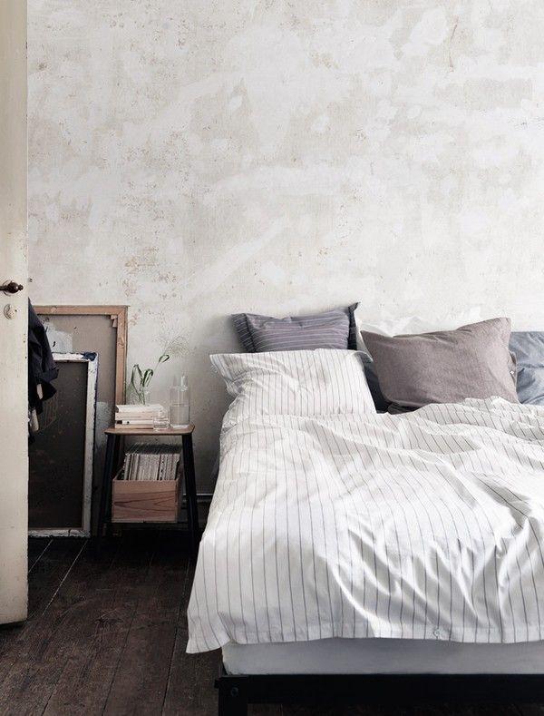 Slaapkamermuur in zachte grijze kleur, met wit en grijs beddengoed