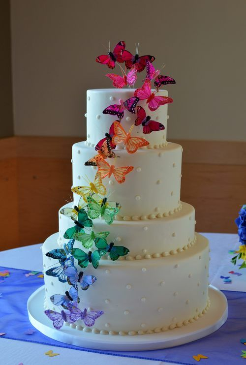 Ivory oval wedding cake with Swiss dots and rainbow butterfly cascade.  Image © Carla Schier