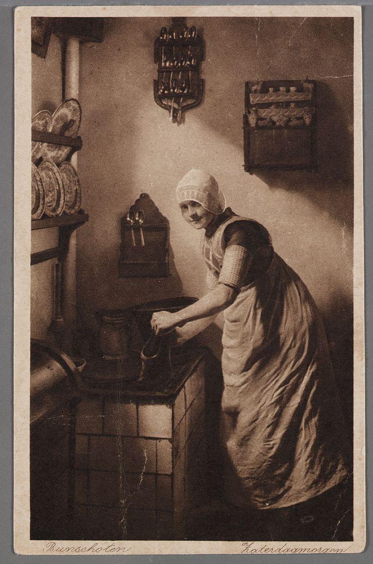 Bunschoten Zaterdagmorgen 1900-1913 Een jonge vrouw staat bij een decoratieve regenbak een klomp te schrobben. Zij draagt een kanten muts, een ongedeelde rode doek, geruite boormouwtjes en een wit schort. Aan de wand hangen lepelrekjes, borden in een rek en een sierkastje. #Utrecht #Spakenburg