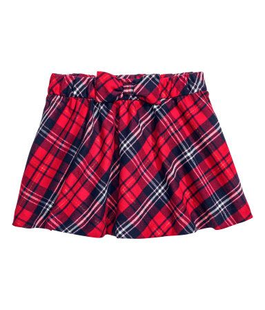Red/plaid. Flared skirt in soft woven fabric with glittery threads. Elasticized waistband with attached, decorative bow. Unlined.