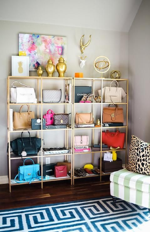 Chic home office also doubles as a closet featuring a wall lined with gold shelving units with glass shelves, Ikea Vittsjo Shelving Unit, lined with designer bags and designer coffee table books.