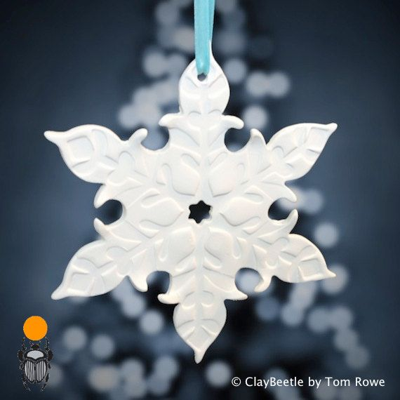 These charming, handmade ornaments are an eggshell white clay without glaze that gracefully hang from a teal blue ribbon. A perfect compliment for