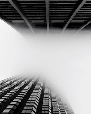 Black and white tall buildings in Chicago disappearing into the fog. Available as poster at printler.com, the marketplace for photo art. Photographer Susanne Kraft.