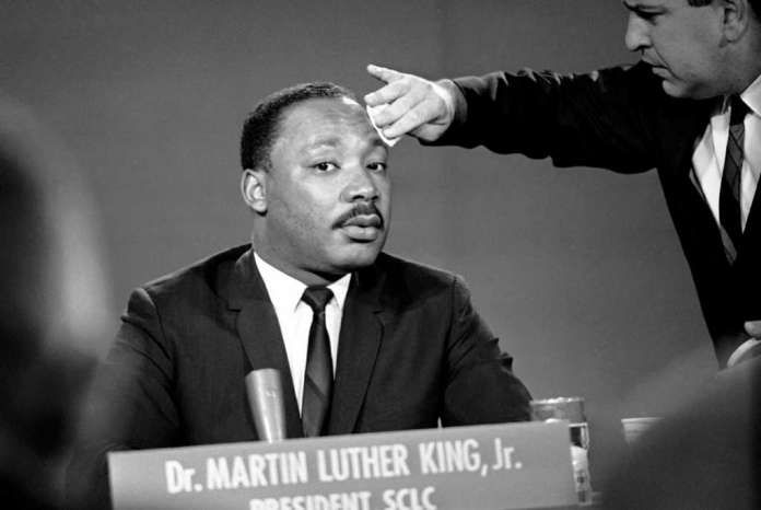 """A makeup man puts a little powder on Martin Luther King's brow before a television program in Washington, Aug. 13, 1957. The president of the Southern Christian Leadership Conference discussed the current racial situation on NBC's """"Meet the Press"""" program. (AP Photo/Henry Burroughs) Photo: Henry Burroughs, STF / Beaumont"""