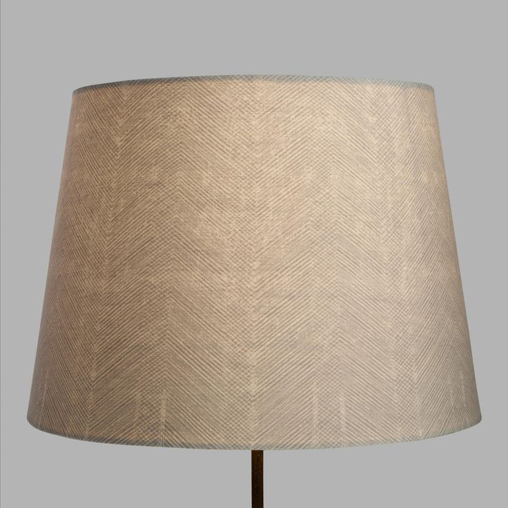 Boasting a finely detailed feathered chevron design in a light gray hue, our exclusive lamp shade has a subtle texture reminiscent of herringbone fabric. Its neutral hue and intricate design element makes it a versatile fit for any of our table lamp bases.