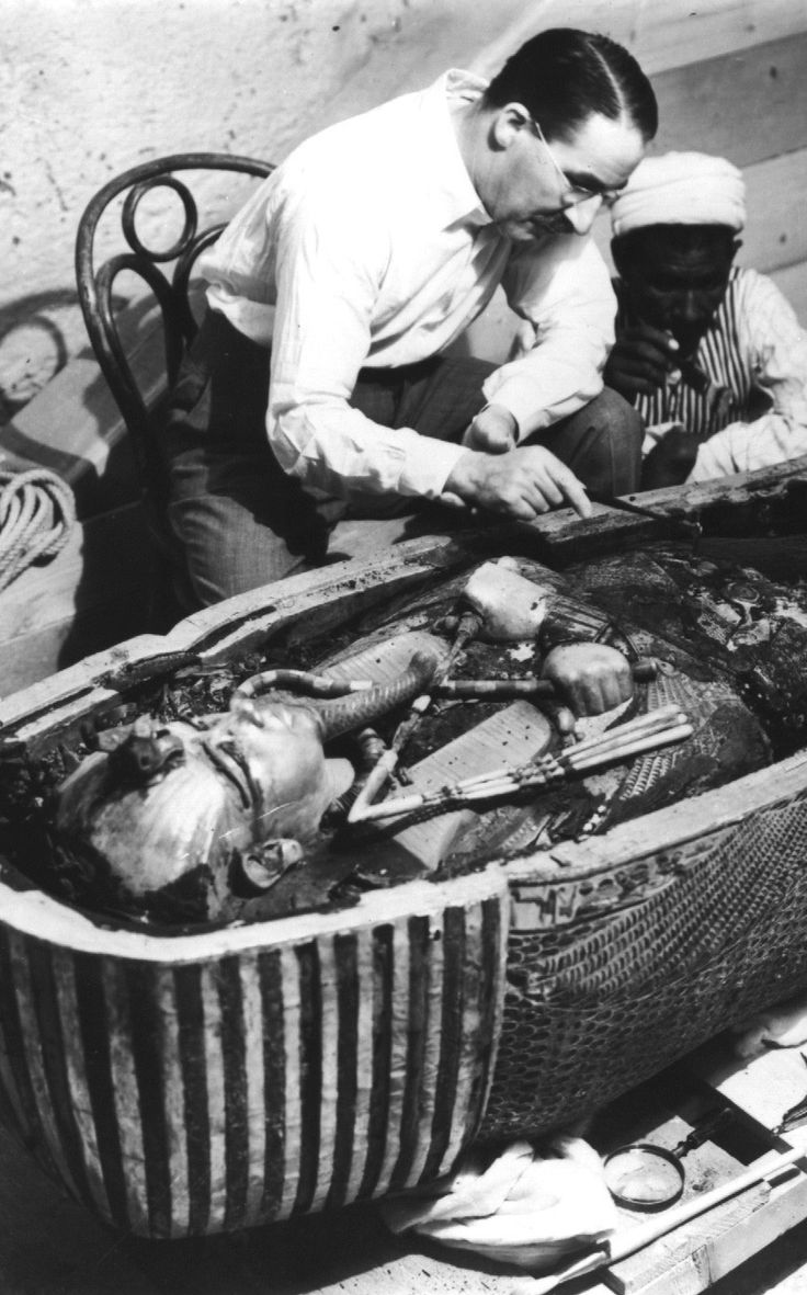 Howard Carter, an English archaeologist, examining the opened sarcophagus of King Tut...