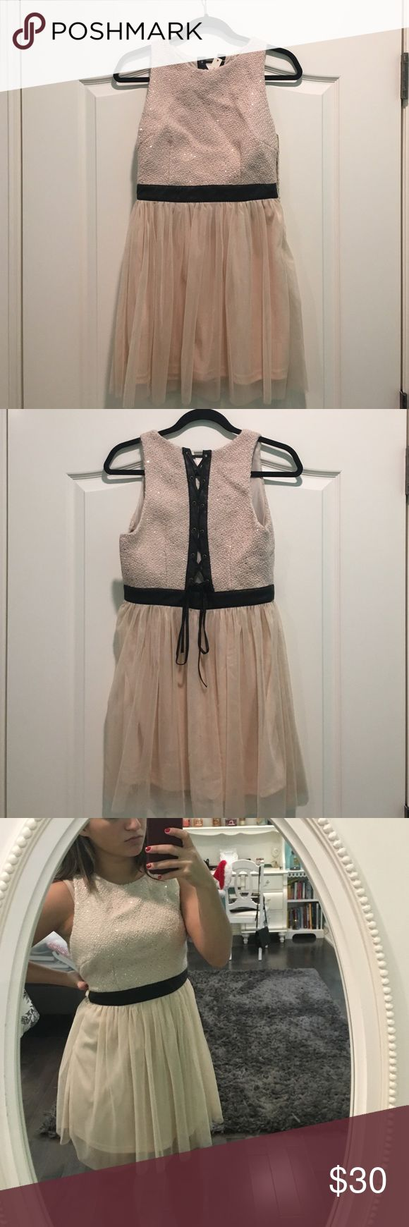 Light pink/Cream party dress NEW! Never worn and still with tags on it. The size is medium but it fits like a small! The material of the black belt and black lace up in the back is leather. Great dress for any special occasion and looks perfect with black shoes and a black bag to match! Mustard Seed Dresses