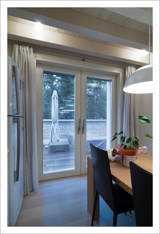 """Alzante scorrevole a due ante all'interno della parete, modello """"MIX"""". Porte interne a filo muro in finitura laccato. Le finestre sono dotate di sensori per allarme. Tende e zanzariere motorizzate con radiocomando. Portoncini blindati con pannellatura interna laccata bianca. - Double concealed lift-and-slide patio door model """"MIX"""". Lacquered flush interior doors. Windows are equipped with alarm sensors. Motorized curtains and flyscreens. Armoured doors with white lacquered interior panel."""
