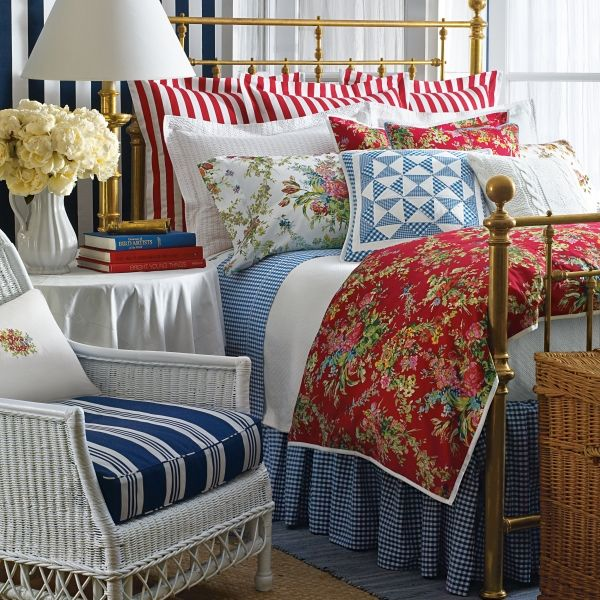 Mixing and matching red, white and blue stripes, floral patterns all works together in this cozy bedroom.