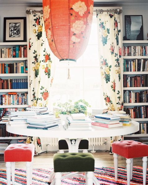 A red paper lantern above a round white table surrounded by upholstered stools.