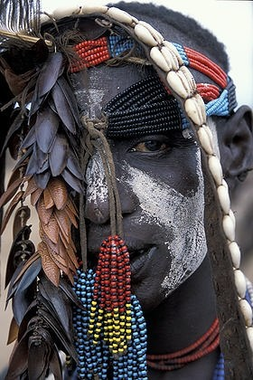 Karo man wears wearing face paint, beads and cowry shells near Omo River in southern Ethiopia. The Karo are an ethnic minority group whose traditional agrarian lifestyle is endangered. The Karo are well known for their adornment