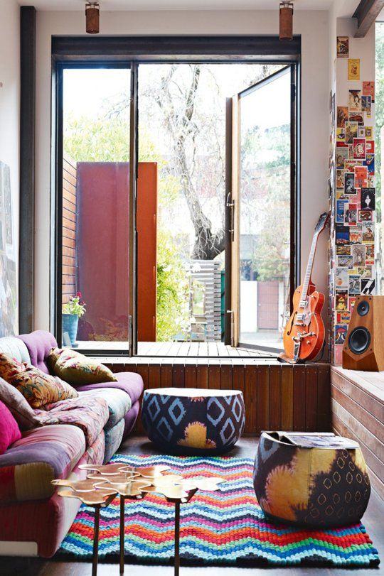 A Riot of Color and Texture in Melbourne.  Guitar, speakers, postcard art and a wall of glass by a colorful comfy couch.