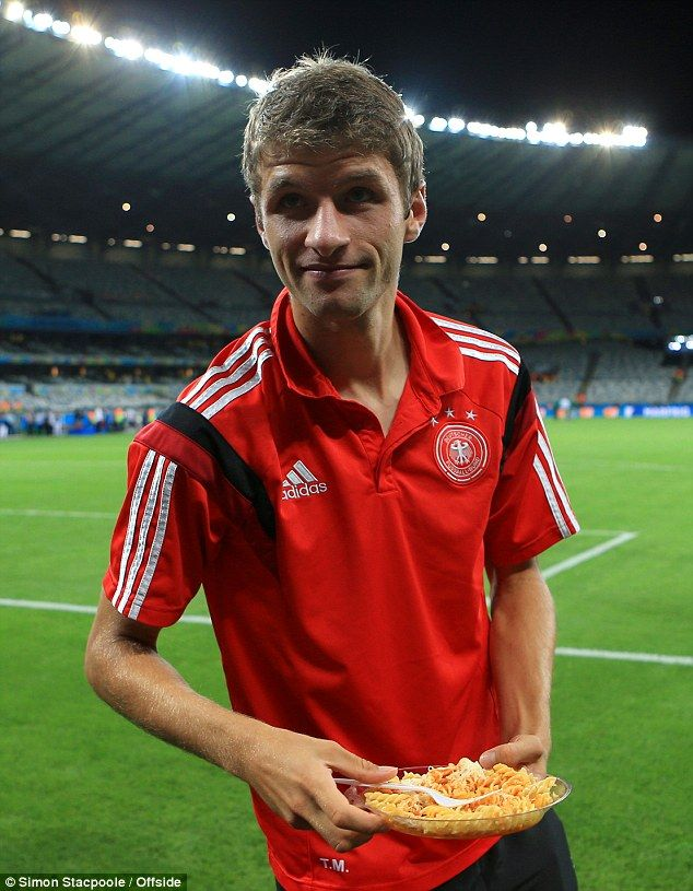 Post-match treat: Thomas Muller eats pasta as he salutes the German supporters after the f...