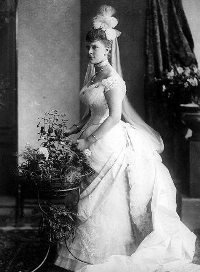 Princess Mary of Teck married George, the Duke of York.  They later became Queen Mary and King George V.  In this wedding photo taken in 1893, she is wearing a gown by Linton and Curtis.