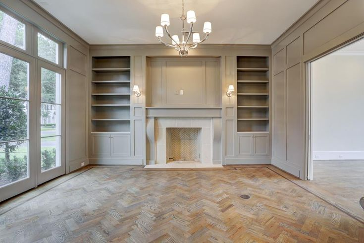 herringbone wood floors, floor to ceiling windows, herringbone brick fireplace, built ins flanking fireplace, millwork on cased opening