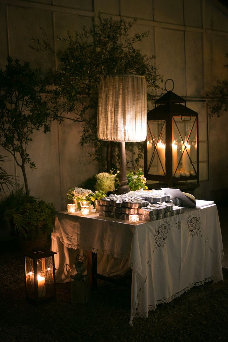 The wedding favors display softly lighted by lanterns, candles and an bat-jour. A nice corner dedicated to say goodbye to guests.