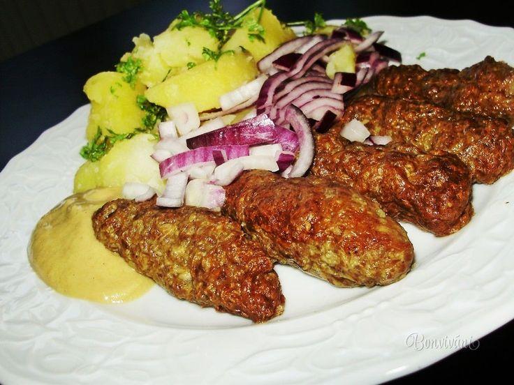 Čevapčiči podľa tohto receptu som sa naučila pripravovať v jednej malebnej bavorskej dedinke, kde som chvíľu pracovala u Srba, dlhodobo žijúceho v Nemecku. Tam sme ich samozrejme robili vo veľkom, z troch druhov mäsa. Mäso sa miesilo z dvadsiatich kíl, to sme mali tak na jeden - dva dni. Zarobené jemne mleté mäso sme nechali do druhého dňa odpočinúť v chladničke.