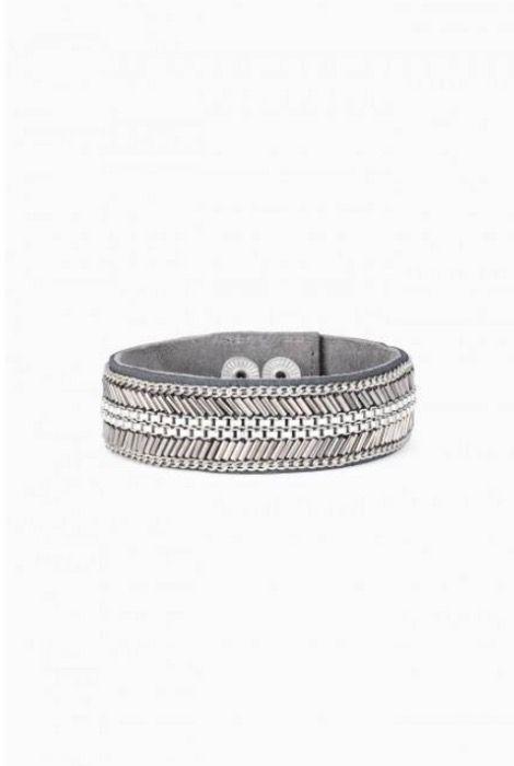 BRACELET CARTER Sur un bracelet de suède, des perles de couleur argentée sont enfilées à la main et entourées d'une délicate chaîne pour former un motif de chevrons. Finition mélange de métaux. Longueur de 20 cm. S'adapte aux poignets de petite à grande taille. Bouton pression.