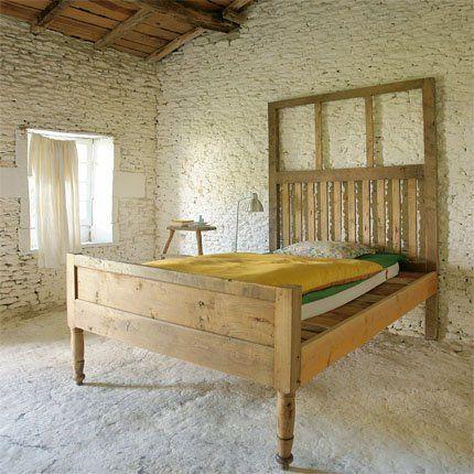 lit en bois, murs de moellons, couverture jaune moutarde, coussin fleuri