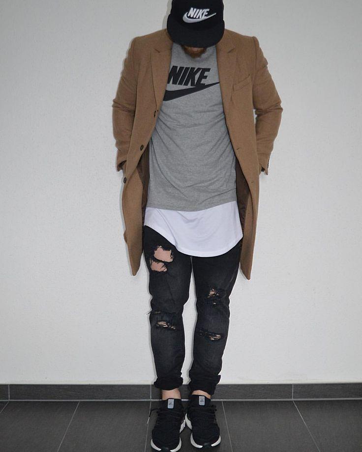 Moda masculina, boné aba reta preto, camiseta linha longa branca sobreposta por camiseta cinza, calça sarja preta rasgada, casaco areia e sapato esportivo preto