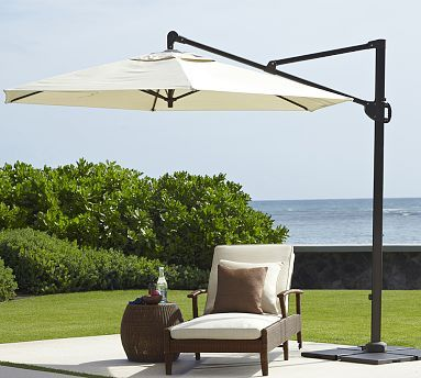 Cream Umbrella With Black Stand On Wheels   One Each Next To Both