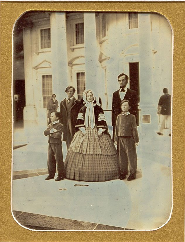 FAKE: Daguerreotype of Lincoln and his family in front of the White House. FACT: This is a modern photo of mannequins at the Abraham Lincoln Library and Museum in Springfield, Illinois (note the man in modern clothes walking in the background.)