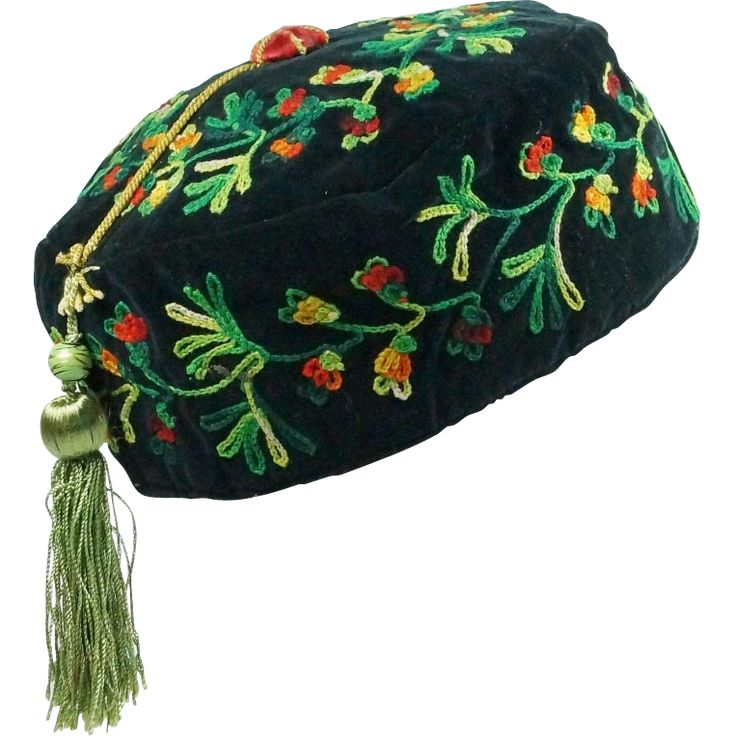 This black velvet cap is very elaborately decorated with trailing tambour work or chain stitch. The meandering flowers are very vibrant in their red, orange and yellow wool. This reflects the massive craze for the newest dyed wool's that were introduced from abroad. The three shades of green are just as cheery. The wooden central button is covered in red silk and then has a cross over star shape of yellow corded cotton attached. This yellow cord attaches half way to a painted green wooden…