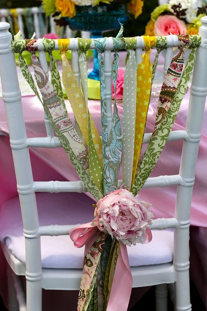 Using Ribbons (or strips of fabric) to decorate a chair for a special event. Tied together with a ribbon flower. Beautiful {Inspiration only}