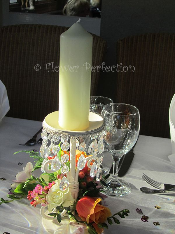 A stunning single candle holder with a cluster of flowers in autumnal colours. Perfect to brighten up long guest tables