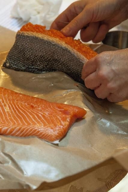 Take your salmon and lay 1/2 of it out, skin side down on top of 1/3 of the salt and sugar mixture on top of the plastic wrap.