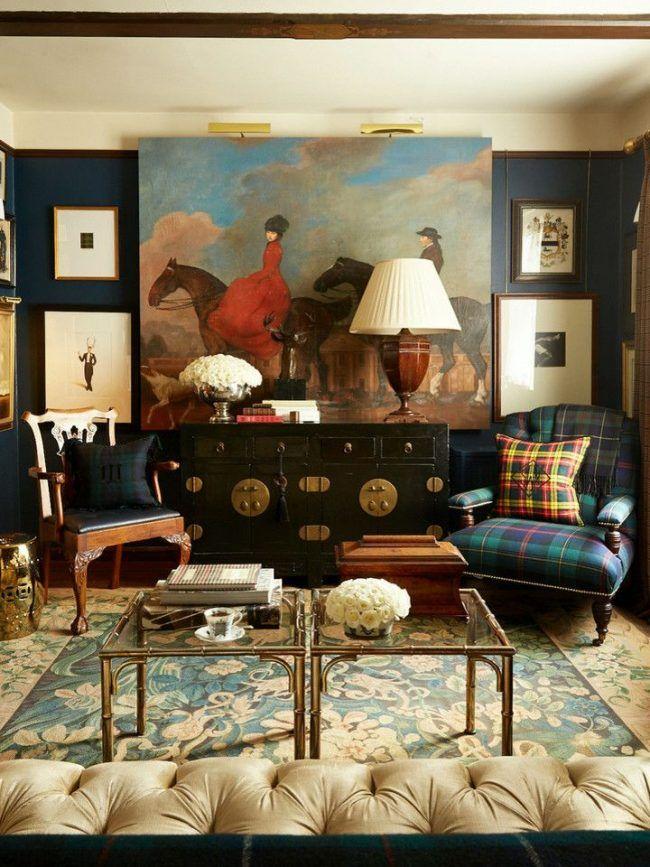 Насыщенные синие обои для традиционной английской гостиной. Клетчатая обивка кресла и подушки с клетчатым принтом – подчеркивающие стиль элементы. Большая картина на центральной стене – изюминка интерьера