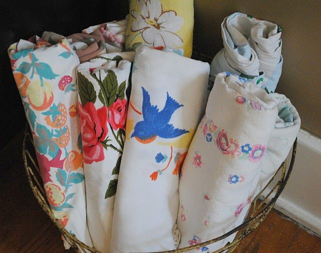 vintage table cloths rolled up displayed in the home...love this idea...