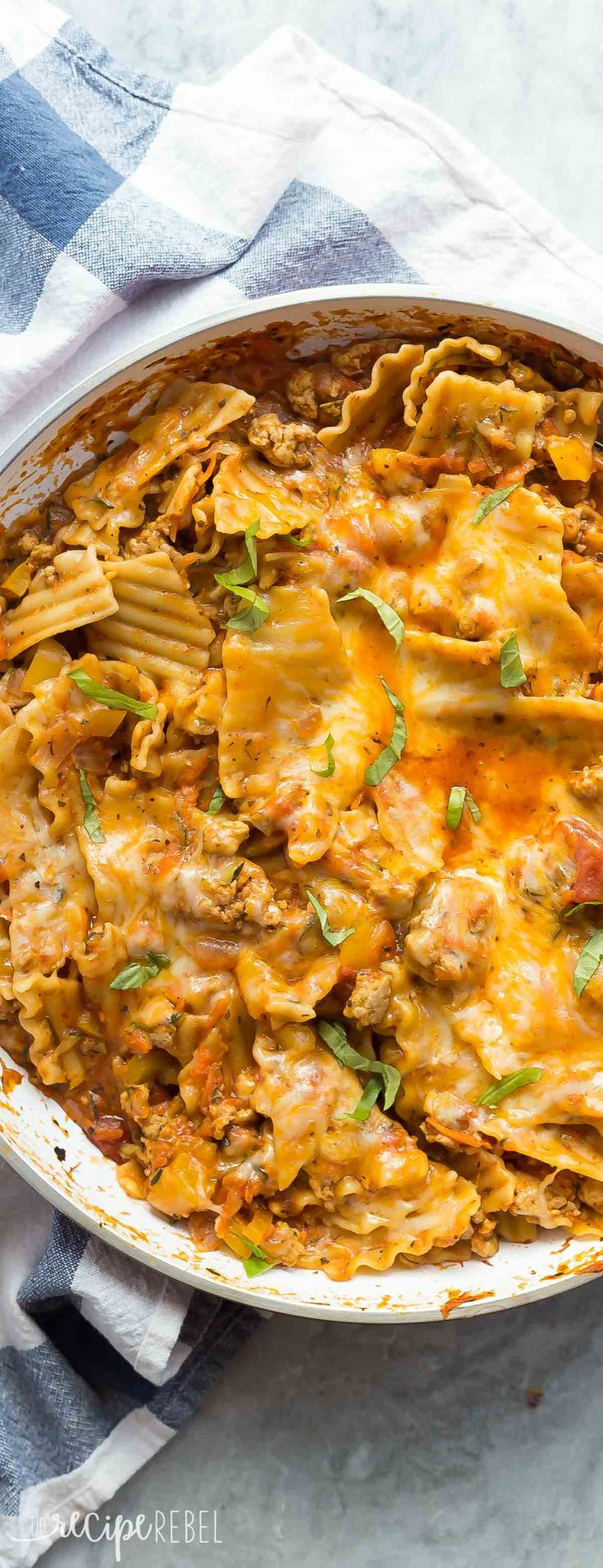This Healthier One Pot Skillet Lasagna is loaded with sneaky veggies, ground chicken or turkey, and a homemade tomato sauce making it an easy, healthy dinner that's ready in 30 minutes! The family will never know ;)