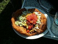 Frybread is a Native American fried flatbread that can be served sweet (with honey, jelly, sugar) or savory (with minced beef and taco toppings).   Ingredients: 4 cups plain flour  2 tablespoons ba…