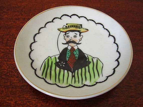 Vintage 50s Lefton China Hand Painted Dish / Man with Mustache and Hat  *Unique small Lefton porcelain china dish with hand painted imagery and details, small for rings or for the collector  *Gold trimmed, manufacturers mark on the back, two holes available in the rear for ease of hanging on the wall  *Good condition, some very slight staining, image is not affected, gold is still present, no chips or cracks, very faint scratching  Measures as follows:  4 diameter x .50 height