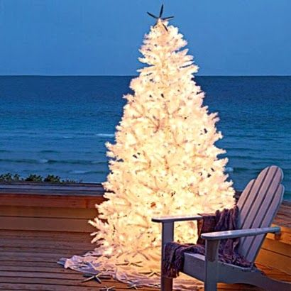 A glowing white Christmas tree by the sea.