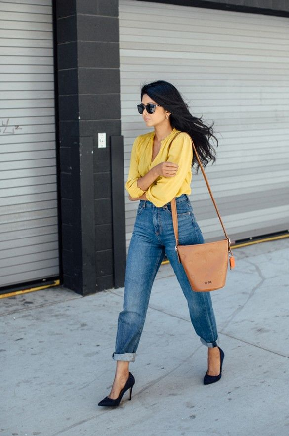 Blogger Walk in Wonderland wears a yellow blouse, high-waisted jeans, black pumps, and a neutral bucket bag