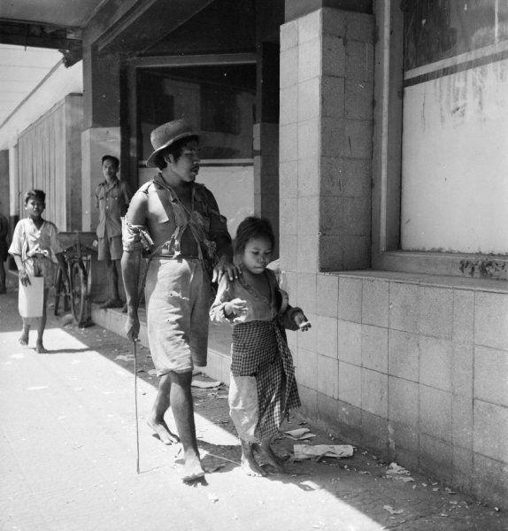 Een jonge man en een meisje lopen in Jakarta over straat, Indonesië (februari 1947)